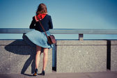 Young woman standing on bridge with her skirt blowing — Stock Photo