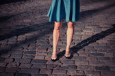 Young woman in skirt walking on a cobbled street — Stock Photo