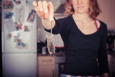 Woman holding a dead mouse in her kitchen — Stock fotografie