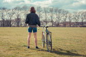 Young woman standing in park with bicycle — Stock Photo