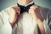 Young man tying a bow tie — Stock Photo