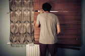 Peeping tom looking through blinds — Stock Photo