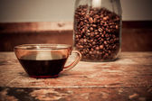 Cup of coffee and jar of beans — Stock Photo