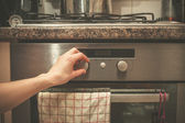 Hand turning knob on stove — Stok fotoğraf