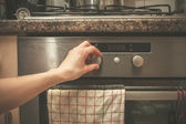 Hand turning knob on stove — Stock Photo
