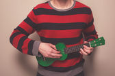 Man in striped jumper playing ukulele — Stock Photo