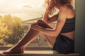 Young woman sitting on window sill on sunny day — Stock Photo