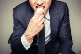 Businessman eating egg — Stock Photo