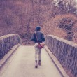 Young woman crossing bridge in forest — Stock Photo #45688727