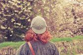 Woman in deerstalker hat looking at trees — Stock Photo