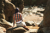 Young woman sitting in a rocky landscape — Stock Photo
