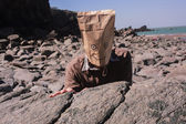 Man with paperbag over his head on the beach — Stock Photo