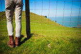 Woman standing by fence in countryside — Foto Stock
