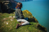 Young woman sitting on edge of cliff — Stock Photo