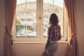 Young woman looking out the window — Stock Photo