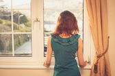 Young woman in dress looking out the window — Stock Photo