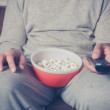 Young man watching television and eating popcorn — Stock Photo #46646839