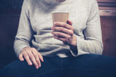 Man with paper cup siting on sofa — Stock Photo
