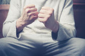 Man on sofa with clenched fists — Stock Photo