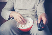 Young man watching television and eating popcorn — Stock Photo