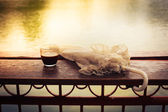 Coffee and umbrella on table by the lake — Stock Photo