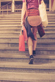 Young woman with shopping walking up stairs — Stock Photo