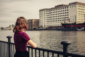 Young woman relaxing by river and looking across at buildings — Stock Photo