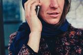 Jonge vrouw op de telefoon buitenshuis — Stockfoto