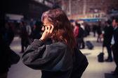 忙しい駅に女性が電話で話しています。 — ストック写真