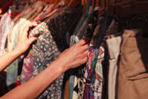 Woman browsing clothes at market — Stockfoto