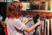 Woman browsing clothes at market — Stock fotografie