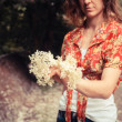 Young woman holding a bunch of elderflowers — Stock Photo