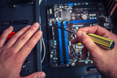 Hand with screwdriver installing computer — Stock Photo