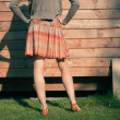 Young woman standing outside wooden cabin — Stock Photo
