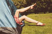 Young woman raising her legs from inside a tent — Stock Photo
