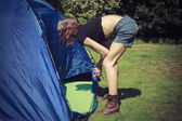Young woman standing outside tent — Stock Photo