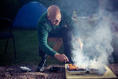 Senior man cooking on a barbecue — Stock Photo