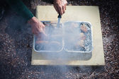 Elderly man attending to barbecue — Stock Photo