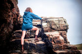 Young woman climbing a rock — Stock Photo