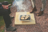 Two people standing around a barbecue outside — Stock Photo