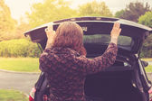 Young woman opening trunk of car — Stock Photo