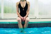 Młoda kobieta siedzi na skraju basenu — Zdjęcie stockowe