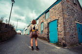 Young woman standing in street outside old house — Stock Photo