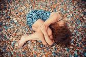 Young woman lying on a pebble beach — Stockfoto
