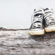 Black sneakers on the old Log wood and gray concrete walls — Stock Photo