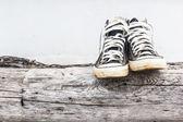 Tênis pretos no antigo log paredes de concreto cinza e madeira — Foto Stock