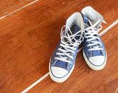 Blue sneakers on the floor wood balcony — Stock Photo