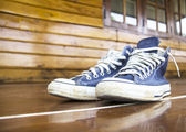 Blue sneakers on the wooden floor — Stock Photo