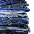 Lot of different blue jeans isolated on white — Stock Photo