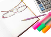 Pencil on a diary with glasses, pens, highlighters and a calcul — Stock Photo